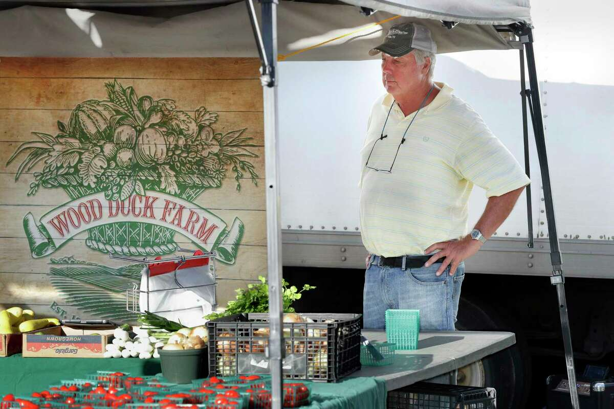 Van Weldon, owner of Wood Duck Farms, looks over the produce on sale at his booth at the Urban Harvest Farmers Market Saturday, Sept. 25, 2021 in Houston, TX. Weldon's farm is located next to a proposed landfill and he is doing everything he can to fight it, including handing out flyers and getting petitions signed at the market.