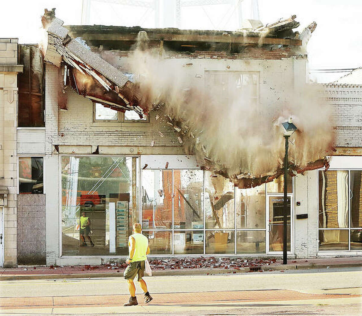 A worker helping to close the first block of West Ferguson Avenue in downtown Wood River Wednesday jumps back as part of the top of a razed building falls to the sidewalk, destroying a street light. City officials recently inspected the building and, upon the advice of an engineer, arranged for it to be razed because of its condition.