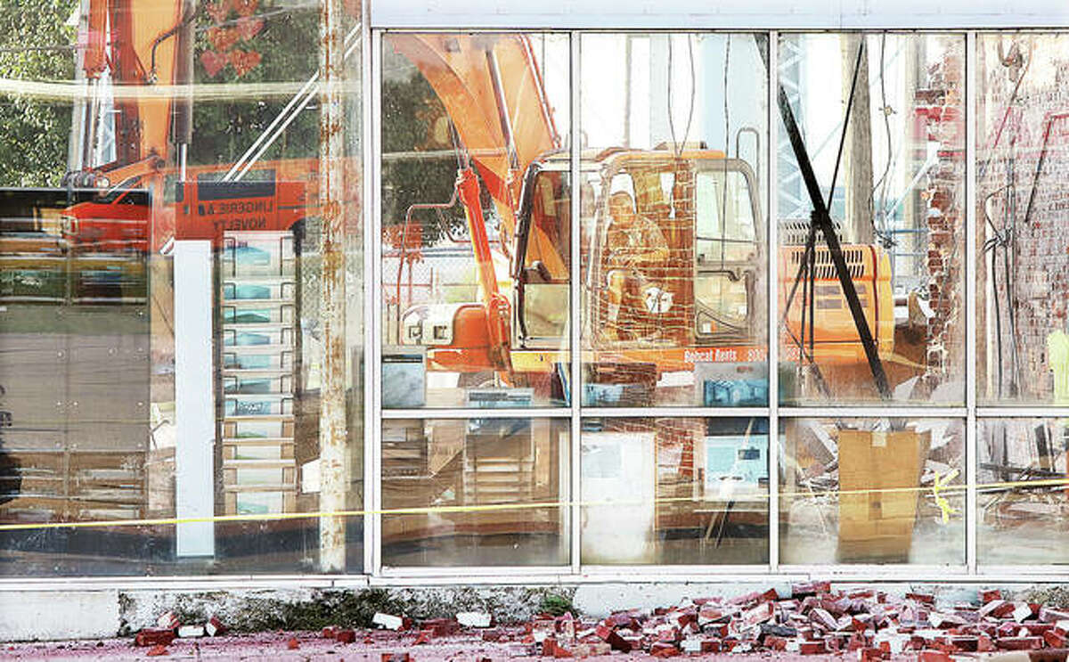A trackhoe operator can be seen through the plate glass windows as he manuevers inside a building being torn down Wednesday in the first block of West Ferguson Avenue in Wood River.