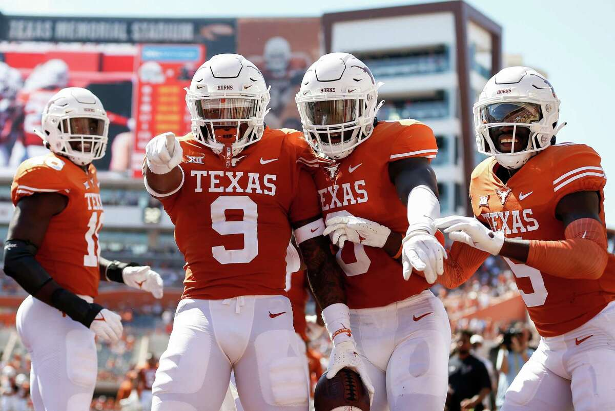 Josh Thompson #9 of the Texas Longhorns celebrates with teammates after an interception return for a touchdown in the second quarter against the Texas Tech Red Raiders at Darrell K Royal-Texas Memorial Stadium on September 25, 2021 in Austin, Texas.