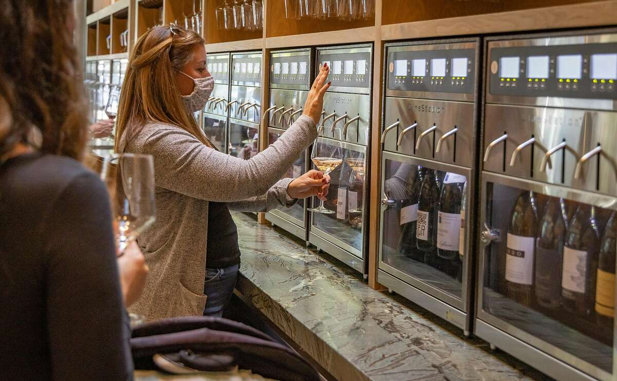 A woman dispenses wine from the wine wall at the Matheson, a new restaurant in Healdsburg.