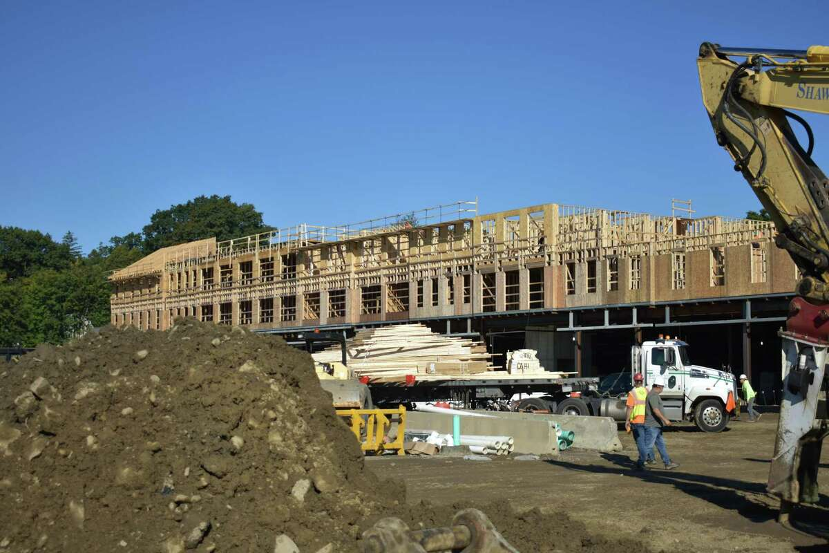 Crews frame a new apartment and retail building in September 2021 in Darien, Conn., opposite the Noroton Heights station of Metro-North and designed for just over 120 units.