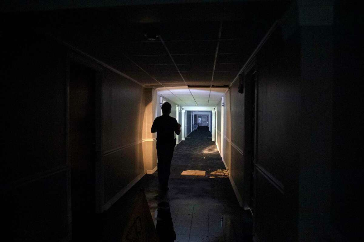 A resident uses a flashlight in a darkened corridor Sept. 4 at an apartment complex in New Orleans, days after Hurricane Ida.