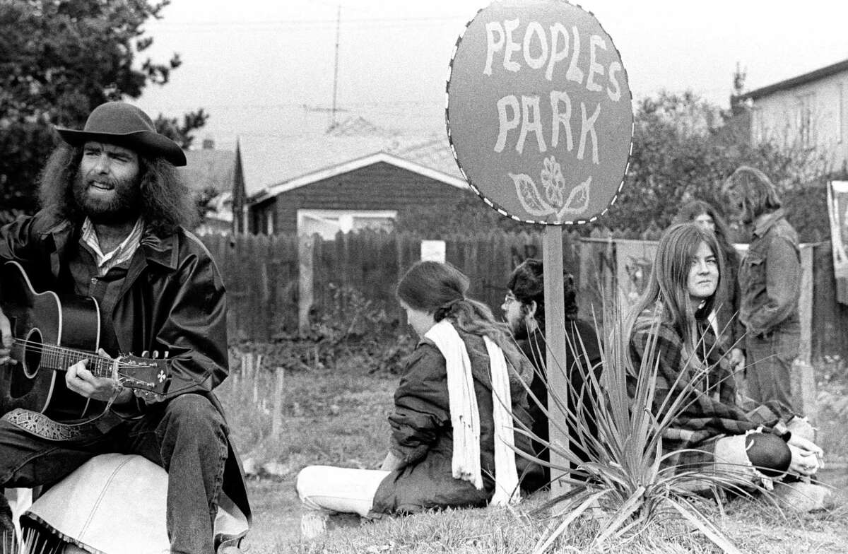 A man plays a guitar as others surround a sign that says People's Park in this circa 1970 photo.