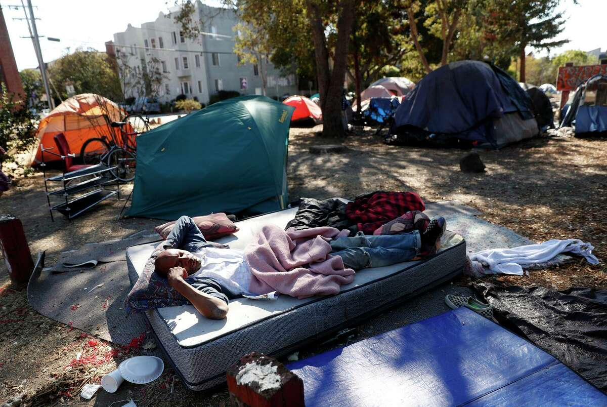 Rusty James Jr. lies on a mattress in People's Park, where UC Berkeley plans to build housing.