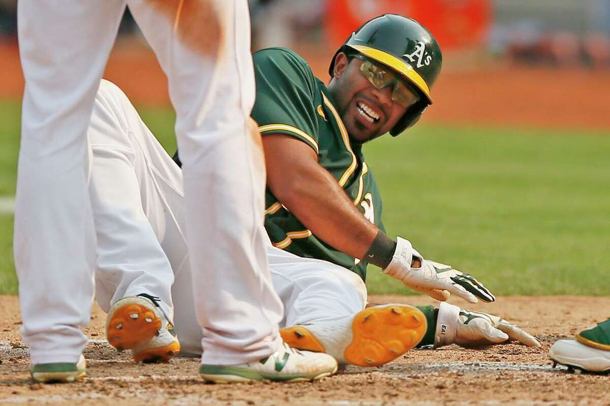 Oakland Athletics Elvis Andrus (17) on the ground as he scored the winning run in the ninth inning during an MLB game against the Houston Astros at RingCentral Coliseum on Saturday, Sept. 25, 2021, in Oakland, Calif. Andrus fell down in pain as he tagged home plate, giving the A's the 2-1 win.