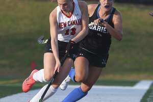 New Canaan's Zoey Bennett (13) brings the ball up the sideline during the Rams' field hockey game against Darien at Dunning Field on Monday, Oct. 19, 2020.