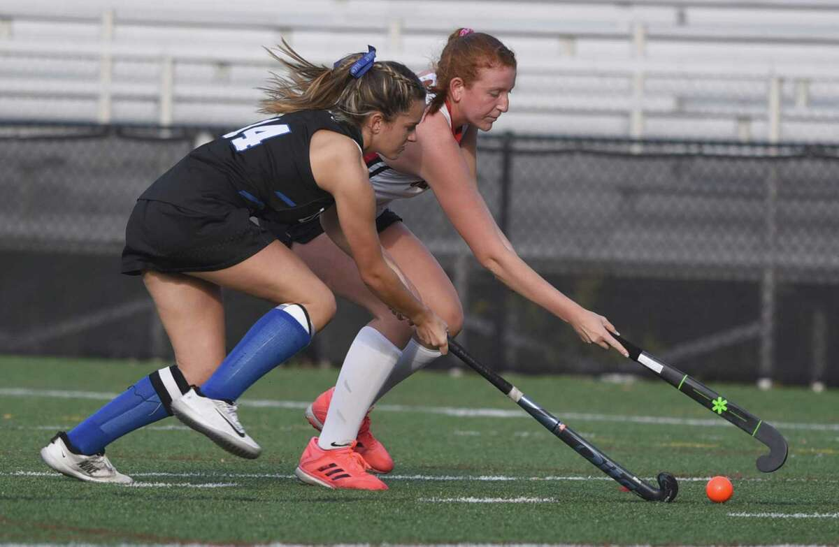 New Canaan's Molly Mitchell and Darien's Emma Riley (14) battle for the ball during a field hockey game at Dunning Field in October 2020.