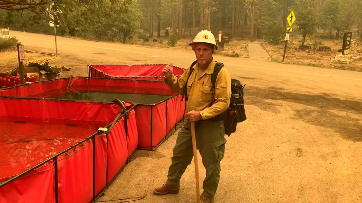 Jeremy Bush, assistant district fire management officer for Sequoia National Forest, with tanks used to store water in the effort to protect giant sequoias from the Windy Fire.