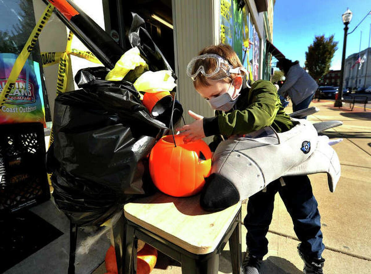 Galaxy Smith, 3, of Edwardsville, gets his candy from a candy shoot while trick or treating on Main Street in Edwardsville Saturday.