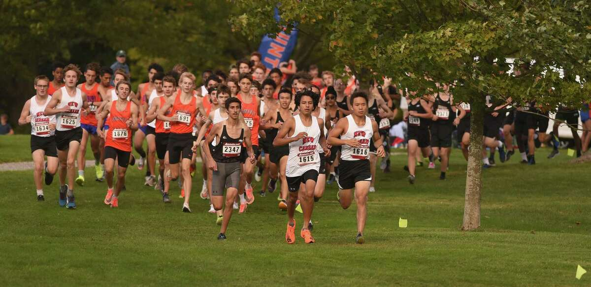 A pack of runners turns down the first hill at the start of a boys cross country meet involving Ridgefield, Trumbull, Danbury and New Canaan in New Canaan's Waveny Park on Wednesday, Sept. 29, 2021.