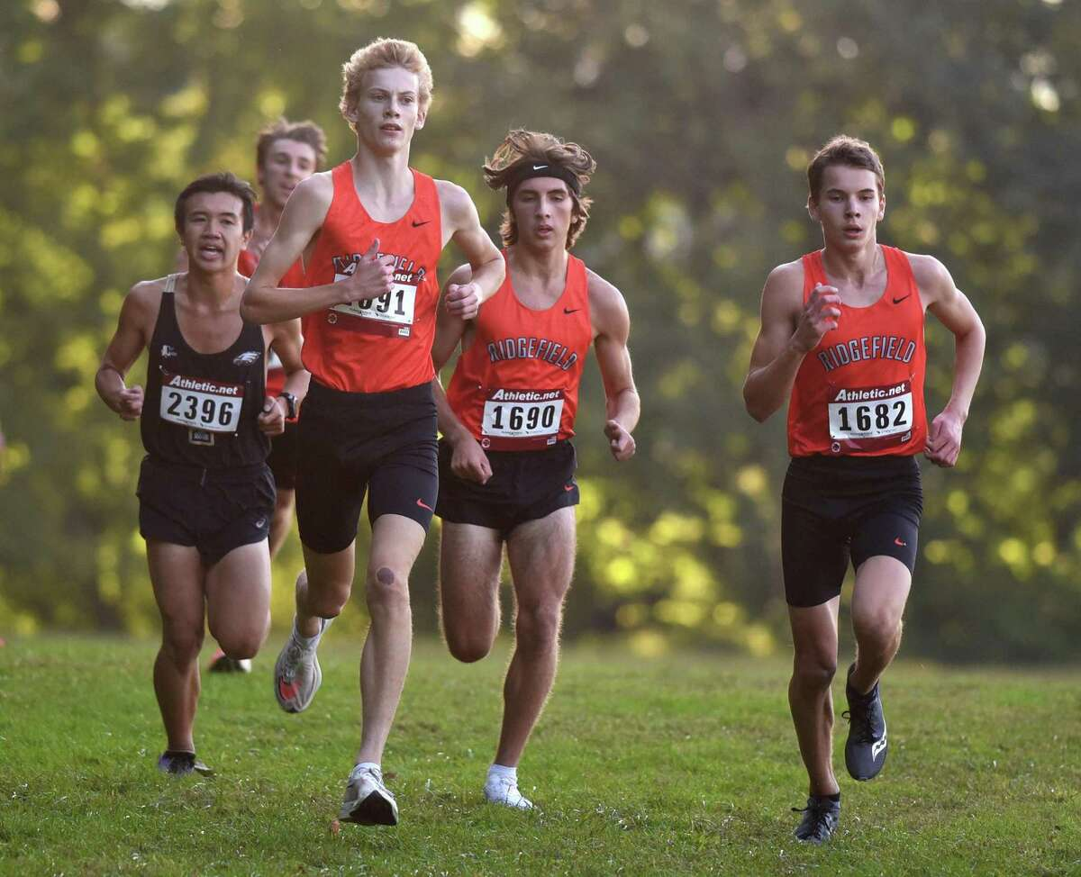 The Ridgefield Tigers, including Benjamin Mikool (1691), Matthew McDonough (1690) and Steven Hergenrother (1682) approach the final hill during a boys cross country meet in New Canaan's Waveny Park on Wednesday, Sept. 29, 2021.