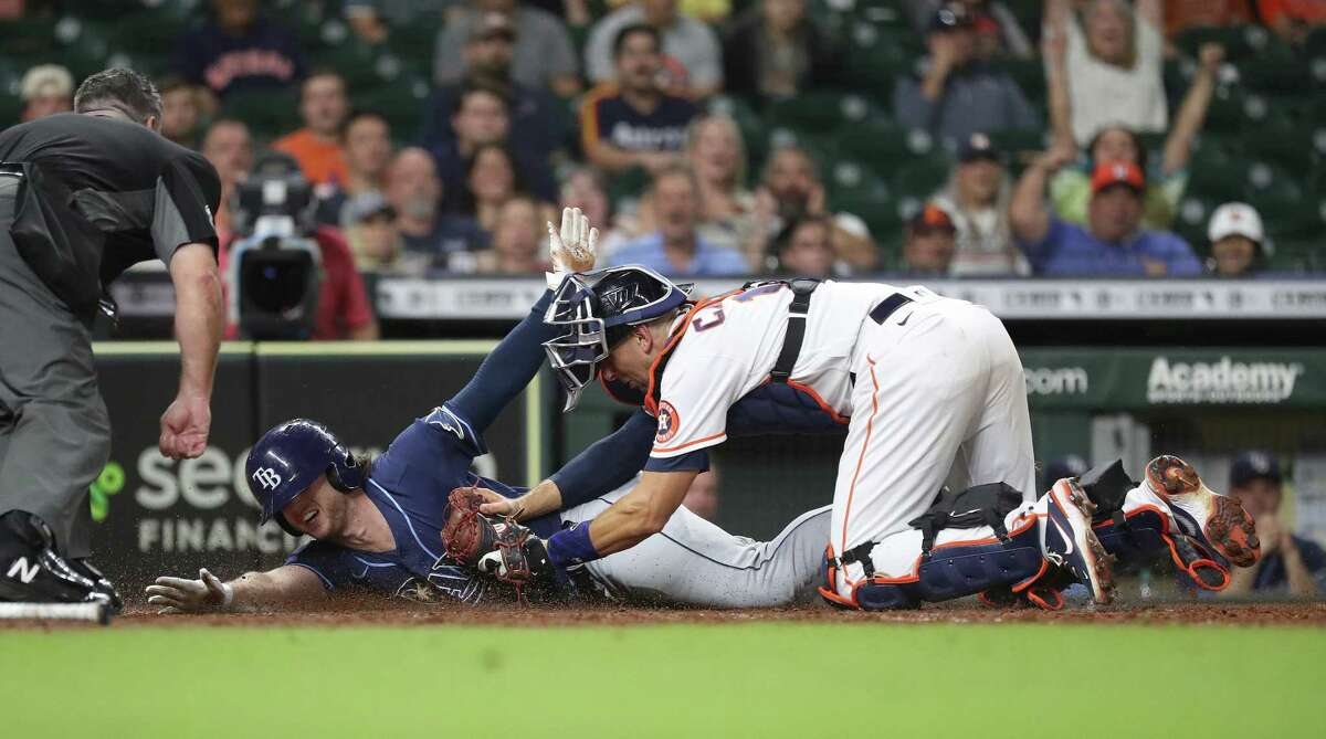 Tampa Bay Rays Brett Phillips (35) dives home as he tried to stretch his triple into an in the park home run, but was tagged at home by Houston Astros catcher Jason Castro during the eighth inning of an MLB baseball game at Minute Maid Park, Wednesday, September 29, 2021, in Houston.
