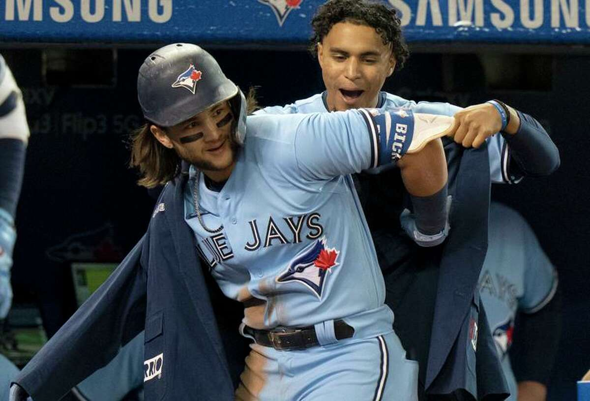 The Blue Jays' Santiago Espinal puts the home run jacket on shortstop Bo Bichette in the third inning.