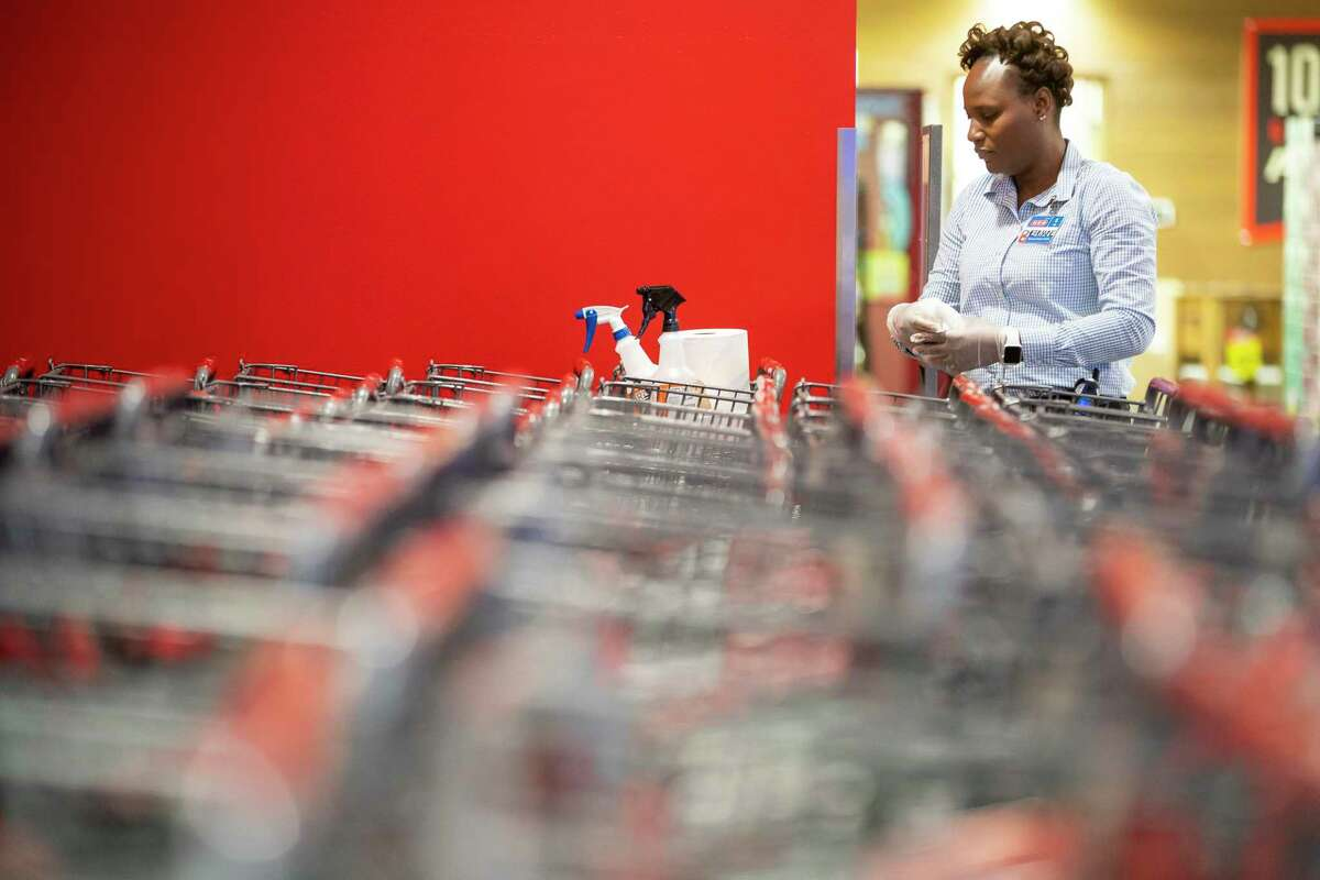 An employee sanitizes carts at the H-E-B in Bellaire. Some essential workers like grocery clerks have found themselves in a health insurance gap.