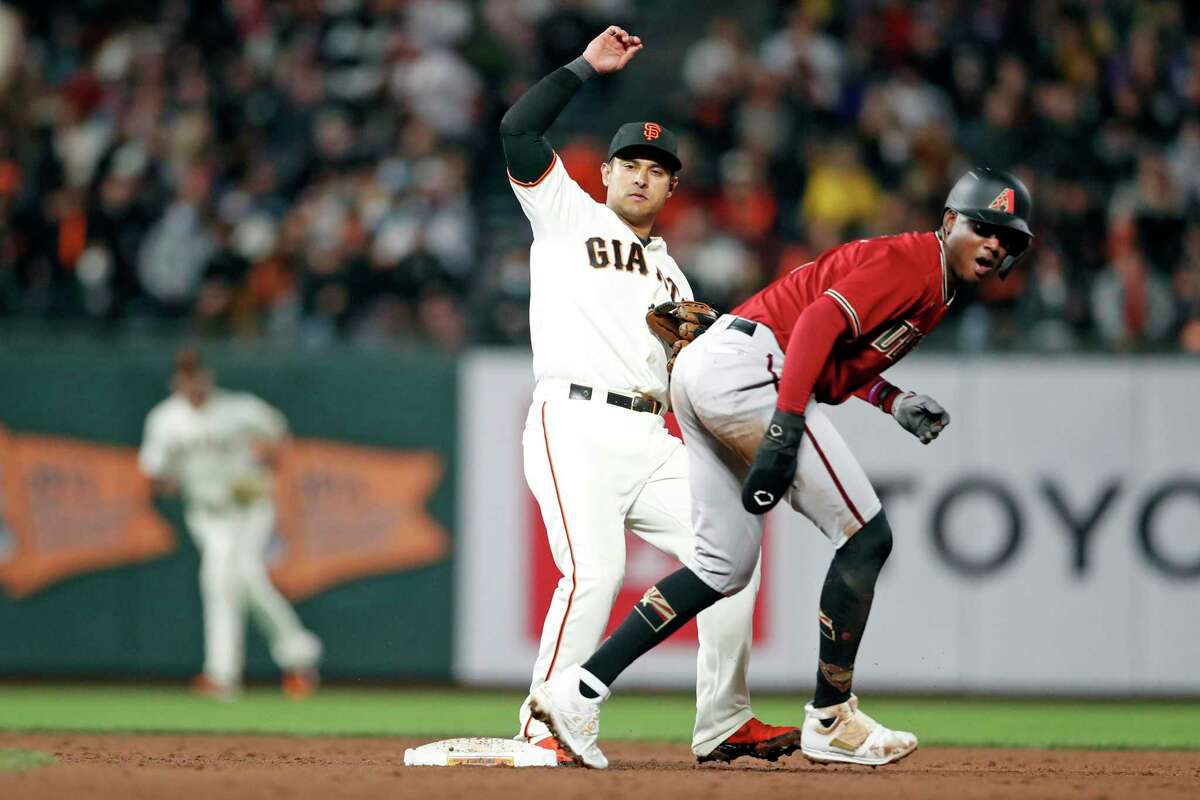 San Francisco Giants' Donovan Solano and Arizona Diamondbacks' Gerlado Perdomo watch as Ketel Marte is out at first base on tail end of double play in 3rd inning during MLB game at Oracle Park in San Francisco, Calif., on Tuesday, September 29, 2021.
