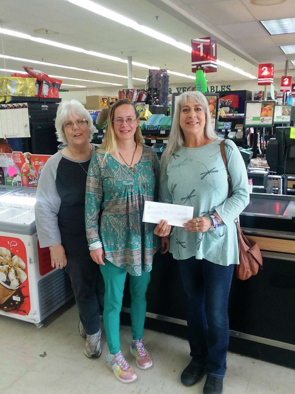 """Bread of Life Pantry director Lynne Mills, far right, accepts a donation of $690 from Houseman's Labor Day """"$1 at check out"""" campaign. Pictured with Mills are Houseman's associates Rebecca French (left) and Cassidy Holtrust."""