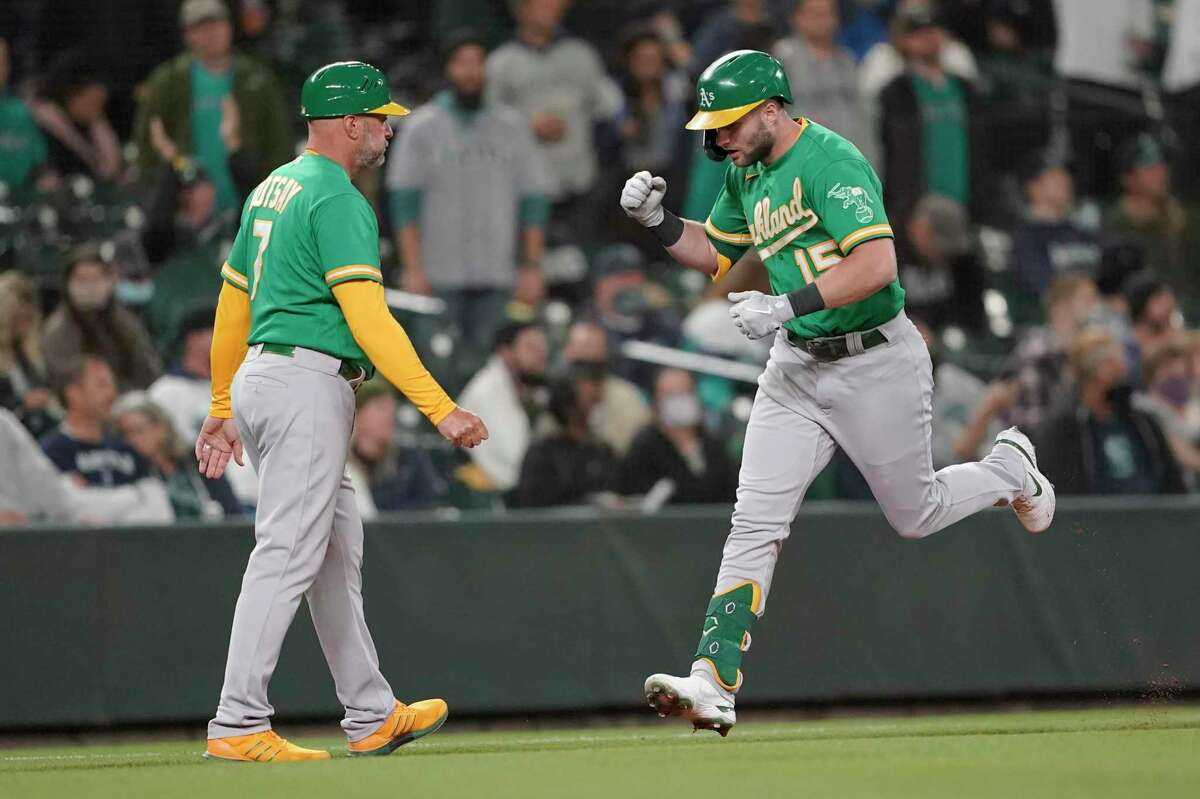 Oakland Athletics' Seth Brown, right, runs past third-base coach Mark Kotsay, left, after Brown hit a solo home run during the seventh inning of a baseball game against the Seattle Mariners, Wednesday, Sept. 29, 2021, in Seattle. (AP Photo/Ted S. Warren)