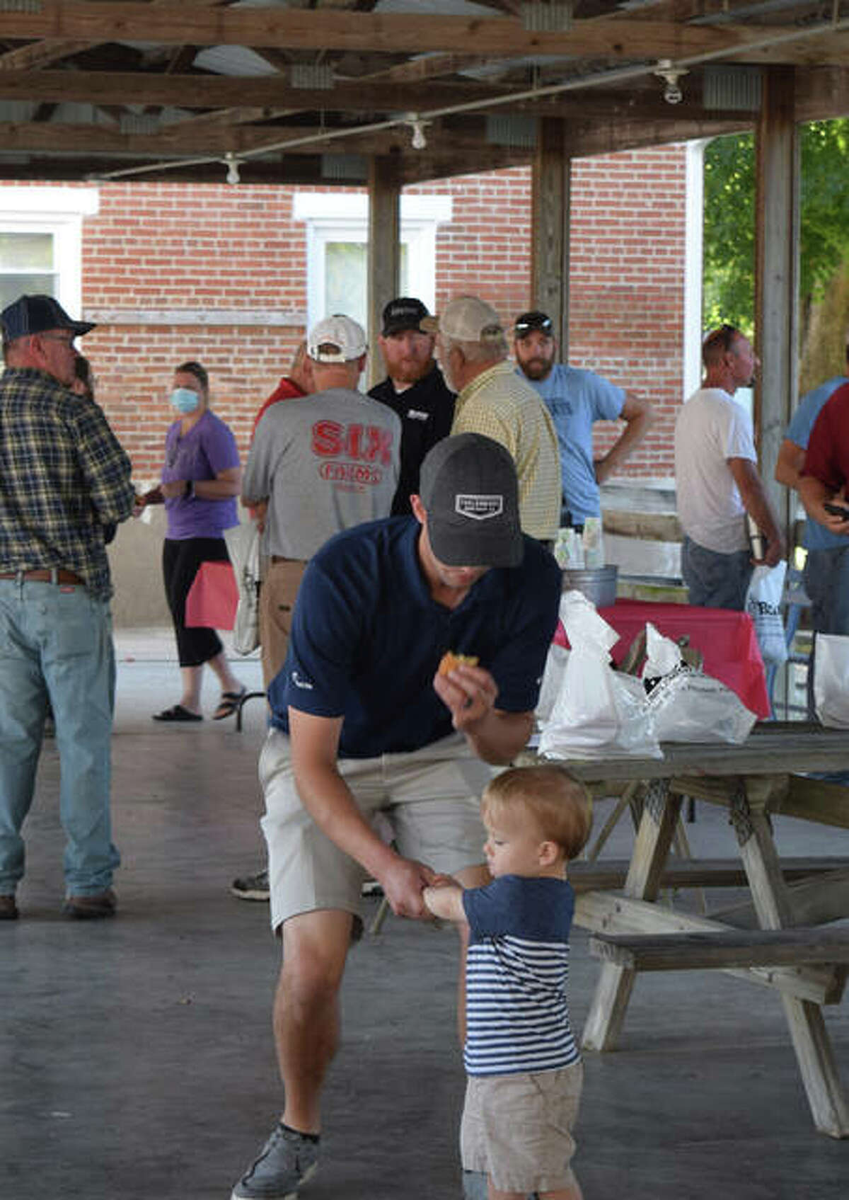 Farmers gather Wednesday at the Arenzville pavillion for a harvest day to remember farmer Matt Roegge, who died earlier this month.