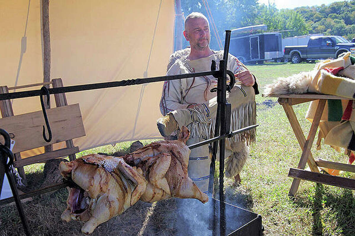 Reenactor Austin Dearing of Kilbourne watches chicken cook the old-fashioned during Old Settlers' Days in Kampsville in 2017. This year's event is Oct. 9-10.
