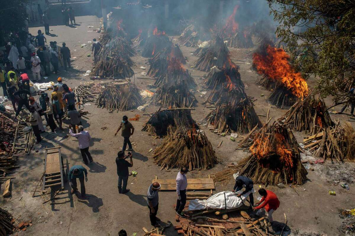 Multiple funeral pyres of victims of COVID-19 burn in an area that has been converted for mass cremation in New Delhi, India, on April 24.