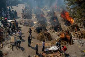 Multiple funeral pyres of victims of COVID-19 burn in an area that has been converted for mass cremation in New Delhi, India, Saturday, April 24, 2021. Authorities are scrambling to get medical oxygen to hospitals where COVID-19 patients are suffocating from low supplies. The effort Saturday comes as the country with the world's worst coronavirus surge set a new global daily record of infections for the third straight day. The 346,786 infections over the past day brought India's total past 16 million. (AP Photo/Altaf Qadri)