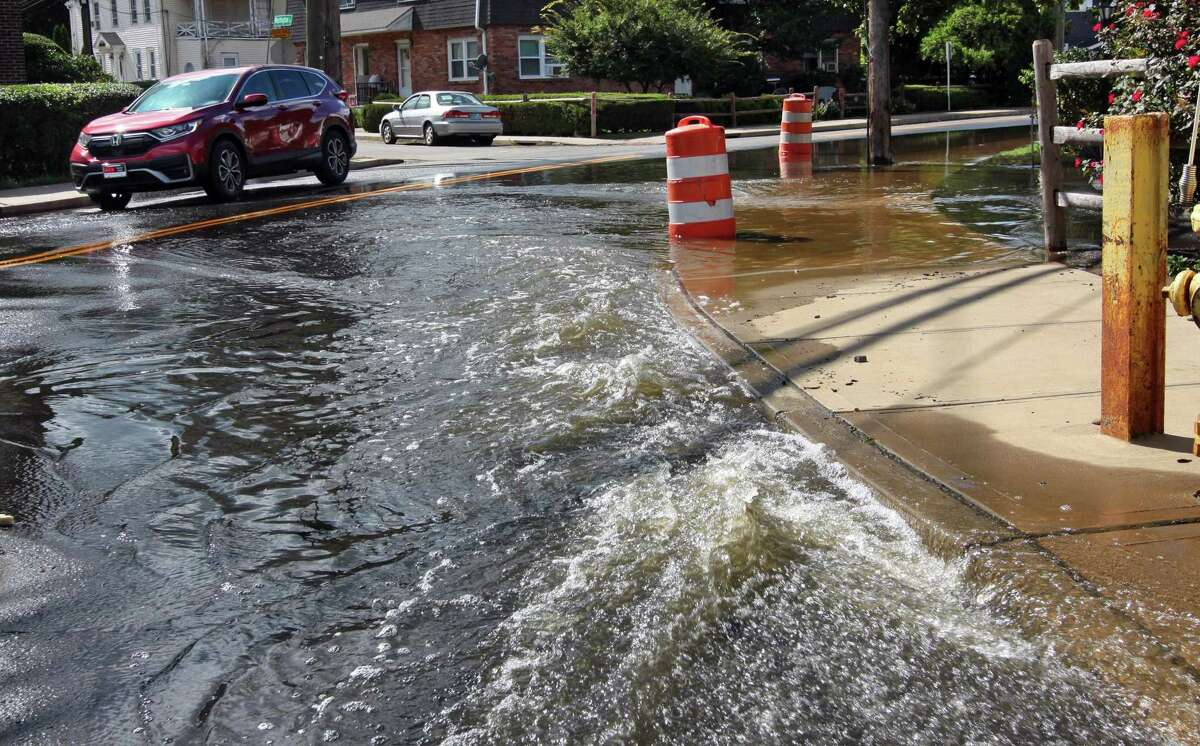 Water flows onto North Street partially flooding it as it is pumped out from an underground parking garage at The Wescott in Stamford, Conn., on Friday Sentember 3, 2021. The remnants of Hurricane Ida pummeled the region on Tuesday causing severe flooding in many spots.