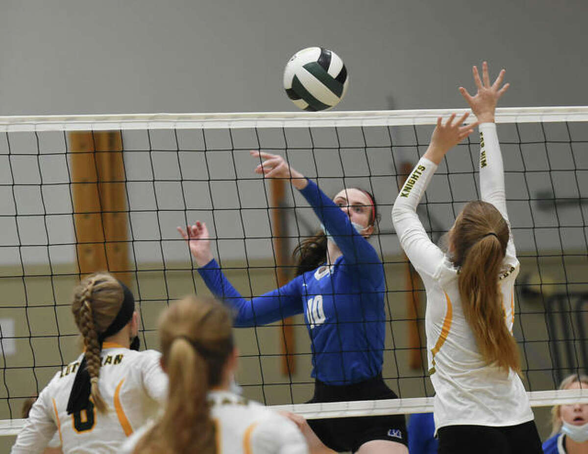 Marquette Catholic's Abby Williams (middle) tips the ball past a Metro-East Lutheran block during Wednesday's Gateway Metro Conference volleyball match at Hooks Gym in Edwardsville.