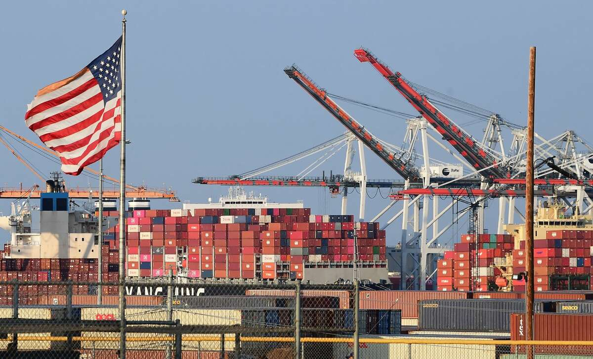A US flag flies near containers stacked high on a cargo ship at the Port of Los Angeles on September 28, 2021 in Los Angeles, California. (Photo by FREDERIC J. BROWN/AFP via Getty Images)