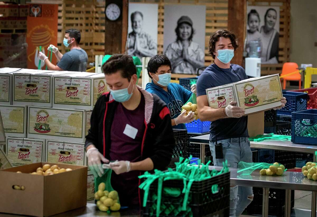 In this photo from April 1, 2020, Jose Secundino, center in a blue sweatshirt, joins fellow recently hired Second Harvest Food Bank of Orange County temporary employees, who have been laid off from restaurant jobs due to the coronavirus pandemic, as they pack boxes of food for the needy. Volunteers then picked up the food and delivered it to local senior centers in Orange County. (Allen J. Schaben/Los Angeles Times/TNS)