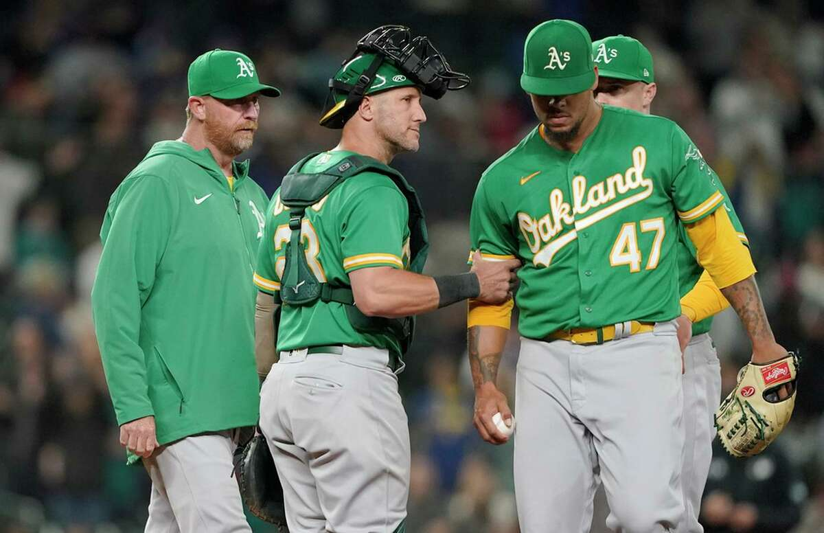 A's catcher Yan Gomes holds the arm of pitcher Frankie Montas (47) after Montas gave up a two-run double Wednesday in Seattle. Both runners who scored had reached on errors.