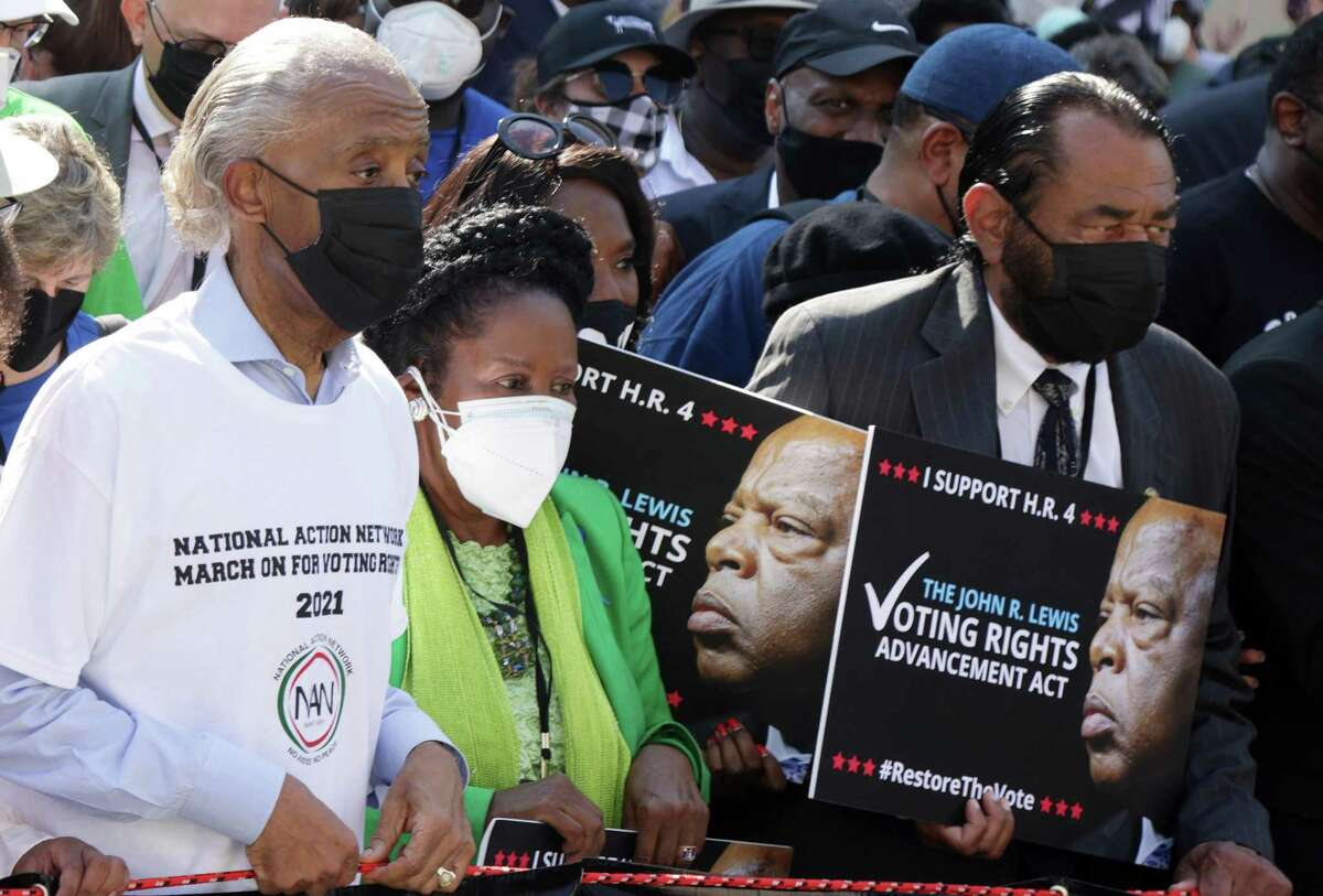 """WASHINGTON, DC - AUGUST 28: The Rev. Al Sharpton (L), U.S. Rep. Sheila Jackson-Lee (D-TX) (2nd L) and U.S. Rep. Al Green (D-TX) (R) participate in a March On For Voting Rights August 28, 2021 in Washington, DC. Voting rights activists gathered in Washington to mark the 58th anniversary of the 1963 March On Washington, where Dr. Martin Luther King delivered his """"I Have a Dream"""" speech, and urged the Senate to pass voting rights legislations. (Photo by Alex Wong/Getty Images)"""