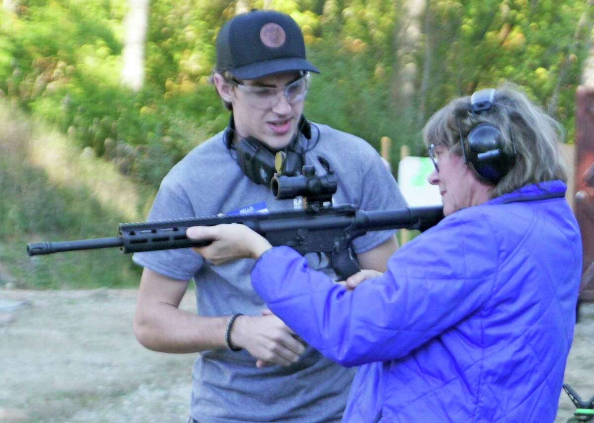 Dana Young gets some tips from a Randy's Hunting Center firearm expert on handling an AR-15 rifle during the Ladies Night event at the Thumb Sportsman's Club gun range on Wednesday evening. (Mark Birdsall/Huron Daily Tribune)