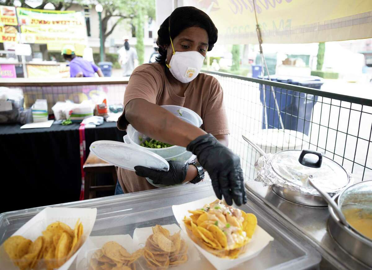 Carla Harris, owner of Mardi Gras's Cajun Cuisine, prepares a bowl of cajun nachos at the 2020 Conroe Cajun Catfish Festival, Friday, Oct. 9, 2020. Harris is originally from New Orleans and travels throughout the state to offer authentic Cajun and creole style foods.