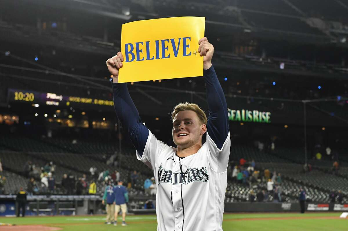 """SEATTLE, WASHINGTON - SEPTEMBER 29: Jarred Kelenic #10 of the Seattle Mariners holds up a """"Believe"""" sign after the game against the Oakland Athletics at T-Mobile Park on September 29, 2021 in Seattle, Washington. The Mariners won 4-2. (Photo by Alika Jenner/Getty Images)"""
