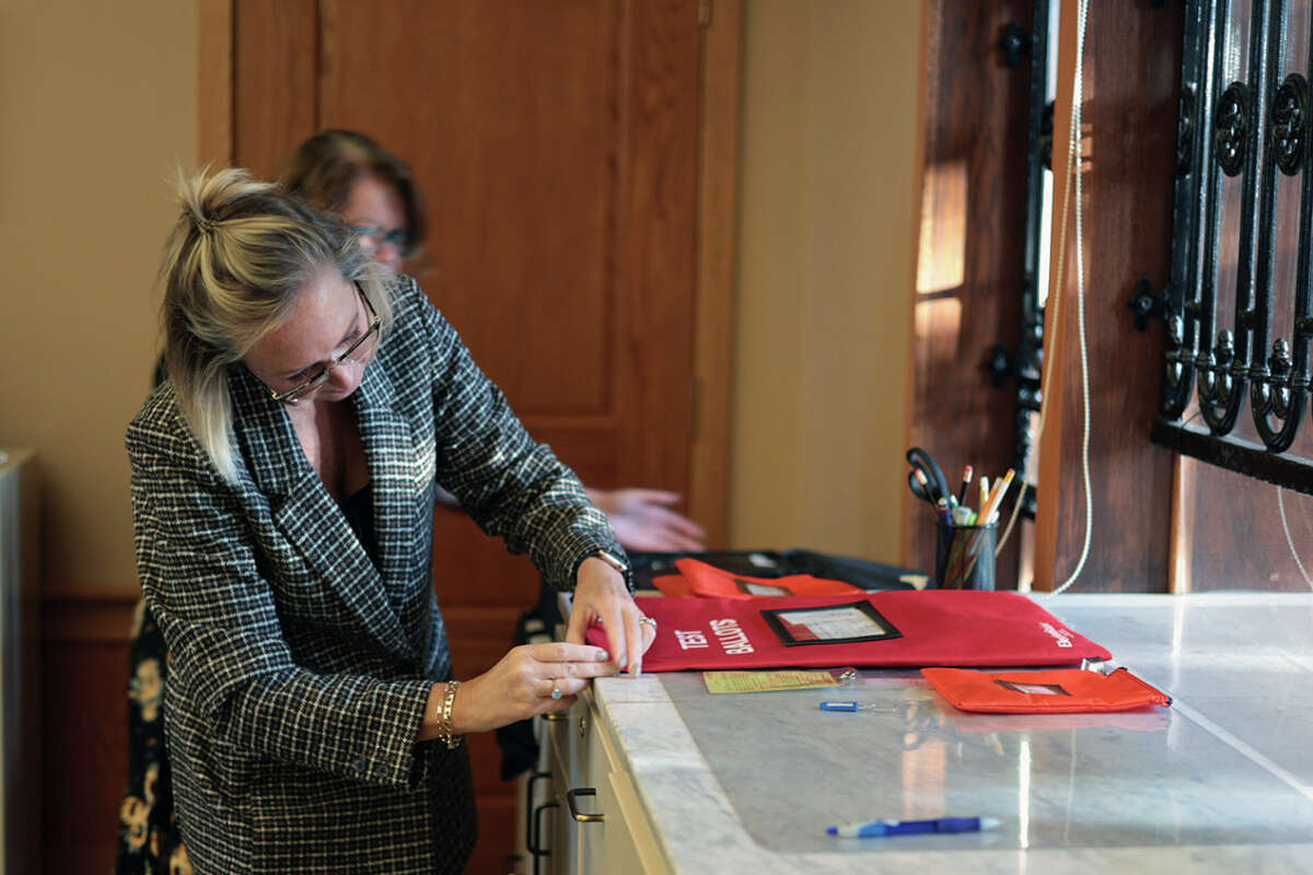 Manistee City Clerk Heather Pefley opens a bag with sample ballots for a public accuracy test held Thursday at city hall on voting equipment for the upcoming municipal election in November.