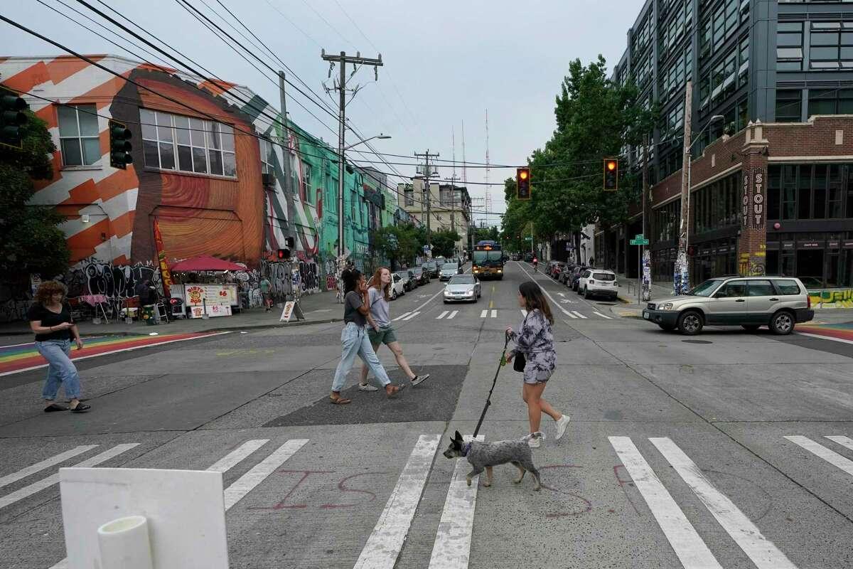 Pedestrians cross Pine Street, Saturday, July 31, 2021, near the Seattle Police Dept.'s East Precinct in Seattle. (AP Photo/Ted S. Warren)