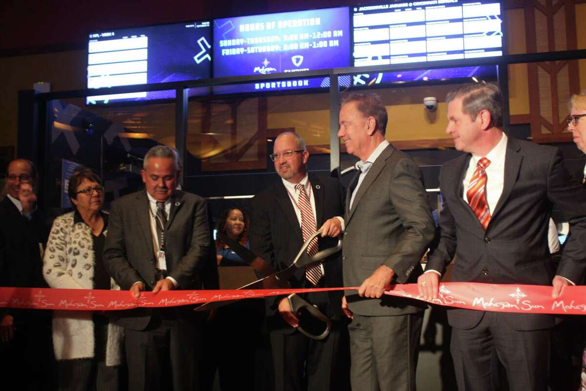 Gov. Ned Lamont helps cut the ribbon to open the Mohegan Sun FanDuel Sportsbook on Thursday, Sept. 30. A few minutes later, the governor placed the first legal sports bet in the state's history, wagering $50 on the Connecticut Sun.