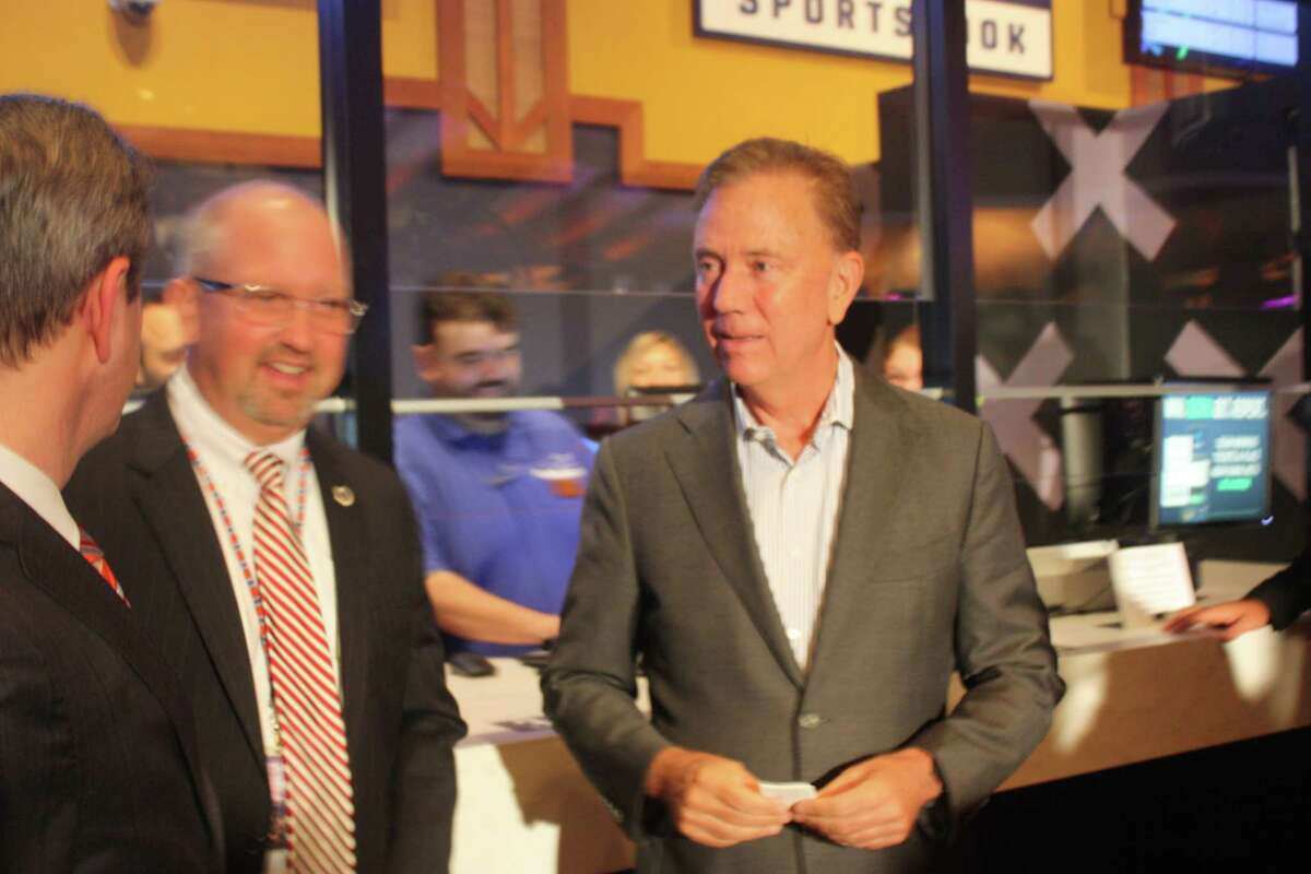 Gov. Ned Lamont holds his betting ticket after placing the first legal sports wager in the state's history: a $50 bet on the Connecticut Sun to defeat the Chicago Sky.