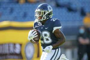Connecticut running back Brian Brewton (28) runs with the ball during the first half of an NCAA football game against Wyoming on Saturday, Sept. 25, 2021, in East Hartford, Conn. (AP Photo/Stew Milne)