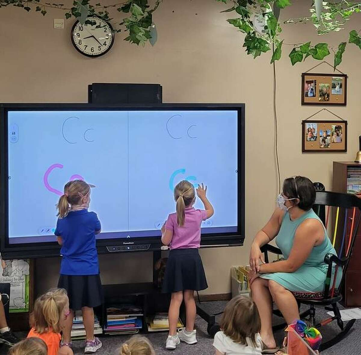 Kindergarten students at Zion Bethalto experiment with the ActivPanel's Vellum writing technology. The feature enables users to write on the interactive display with special pens or fingers, and palms of hands can be used to erase.