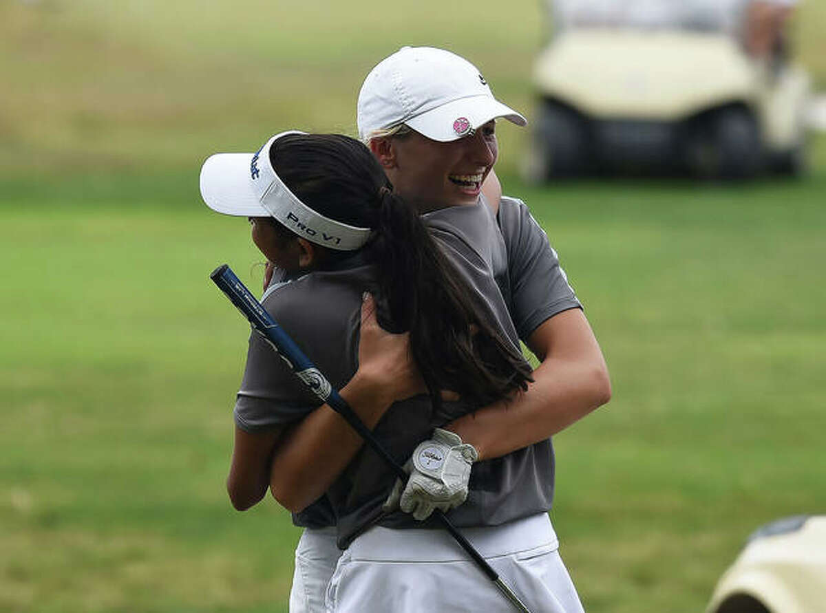 Edwardsville's Morgan Landry, left, is hugged by teammate Ruhee Gupchup after completing her round Thursday in the Class 2A Edwardsville Regional at Oak Brook Golf Club in Edwardsville.