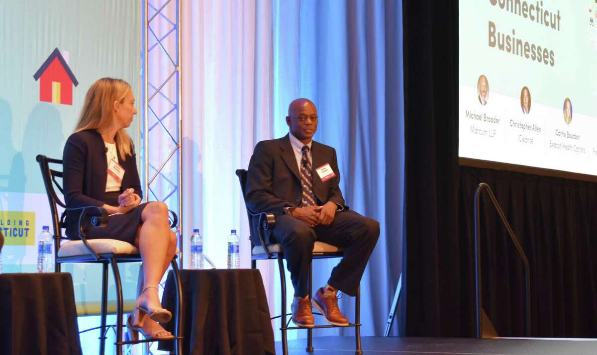 Rohan Freeman, president of Freeman Companies, speaks on Thursday, Sept. 30, 2021, at a Connecticut Business & Industry Association economic conference in Hartford, alongside Carrie Bourdon, chief administration officer of Beacon Health Options.