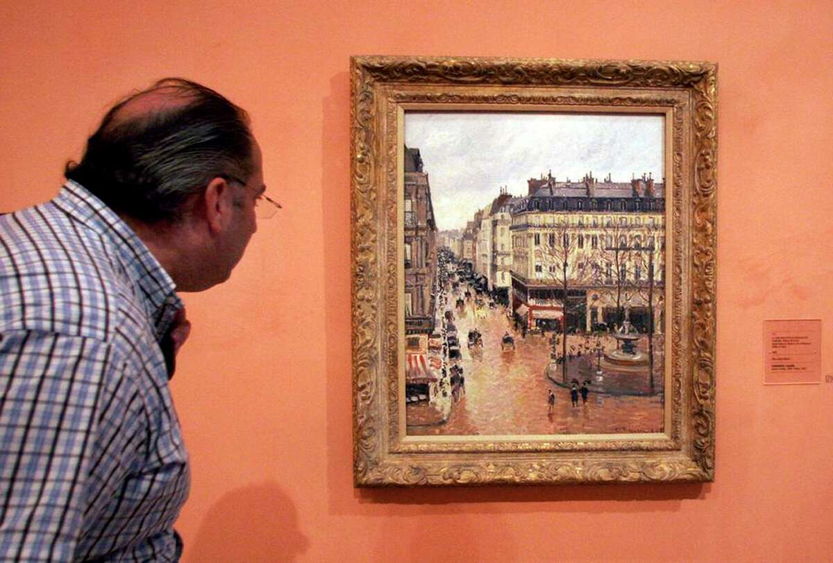 """The Impressionist painting """"Rue St.-Honore, apres-midi, effet de pluie,"""" painted in 1897 by Camille Pissarro, is on display in the Thyssen-Bornemisza Museum in Madrid. The Nazis took the painting from its Jewish owner in 1939."""