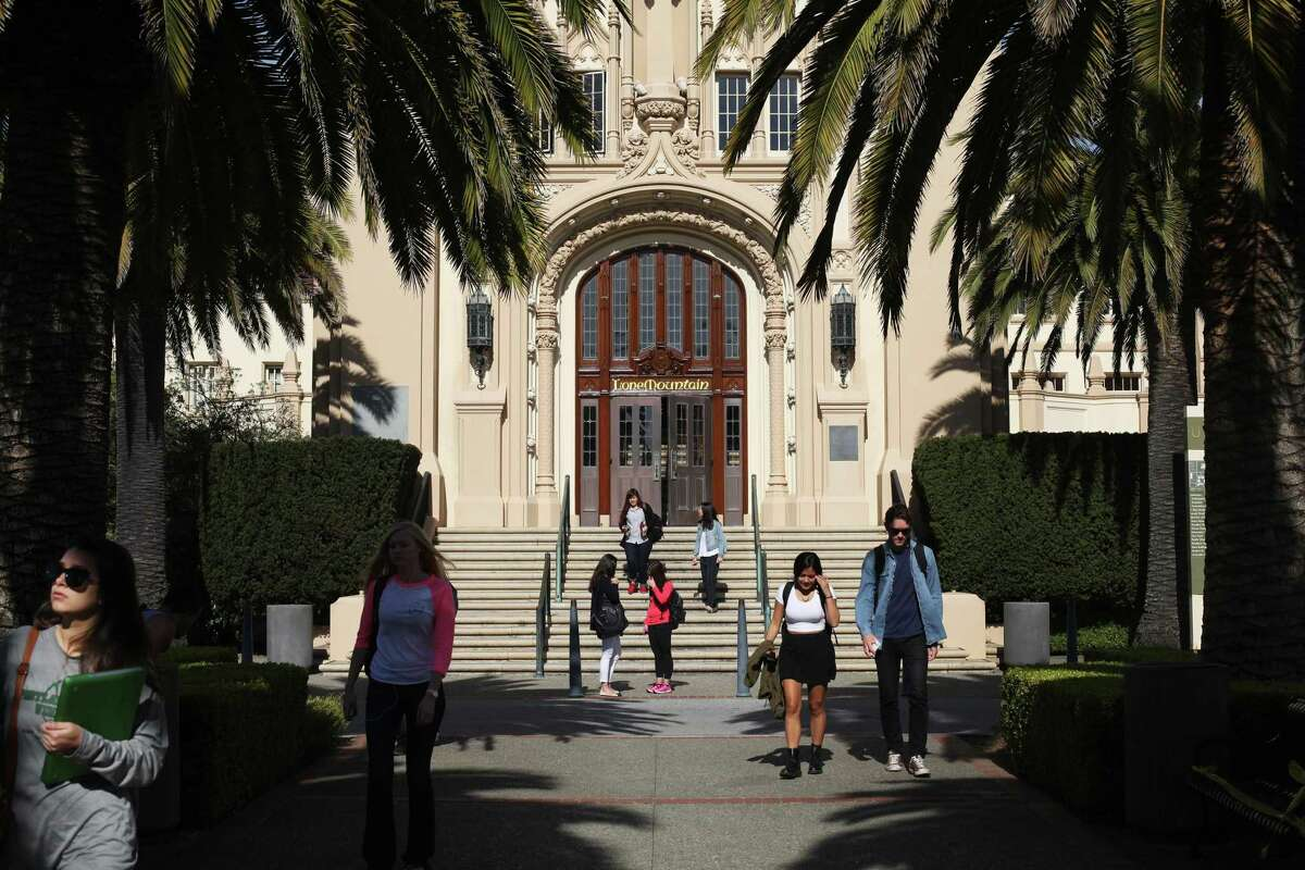 Students walk and mingle in front of the main building on USF's Lone Mountain Campus in 2013.