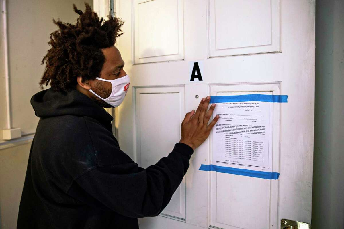 Vandor Hill, 39, looks at a 15-day notice to pay rent or quit his San Francisco apartment.