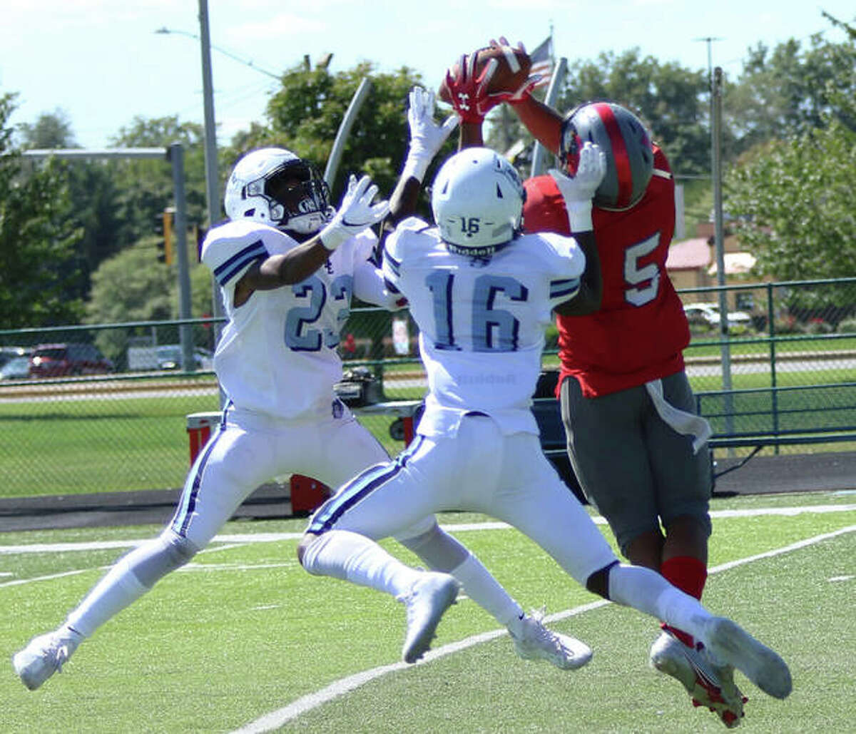 Alton's Keith Gilchrese (5) goes up to catch a long pass above Belleville East defenders Sonny McGill (16) and Javion Mobley Jackson (23) during East's win in last Saturday's Southwestern Conference game in Belleville. The 1-4 Redbirds are back on the road Friday night at Edwardsville.