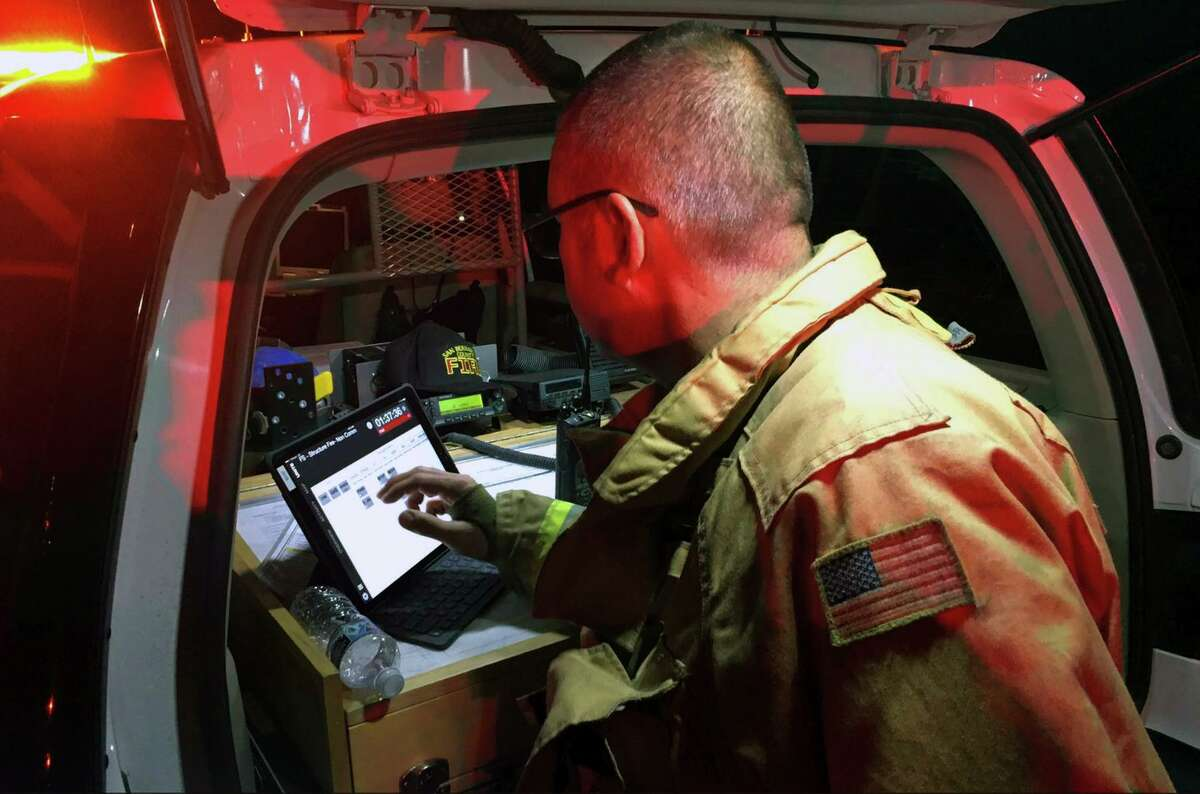 An incident commander in San Bernardino County uses Tablet Command from the rear of his vehicle, where fire tactics and strategies are often determined by the command team.