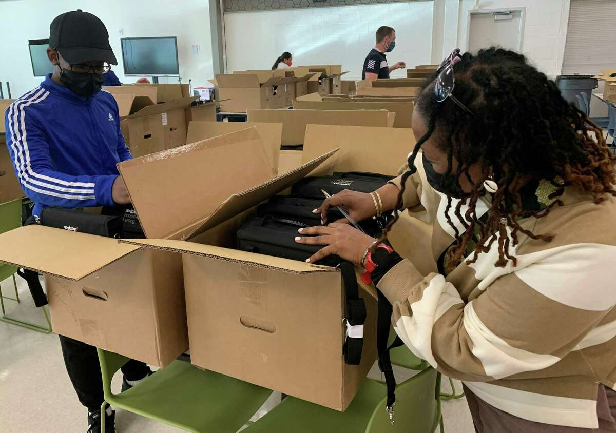 Howard McIntosh, 12, and his mother Kimberlin Hamilton search for his new Chromebook at Ponus Ridge STEAM Academy on Wednesday, Sept. 29, 2021. Each student at the middle school received a new device through a partnership with Verizon Innovative Learning.
