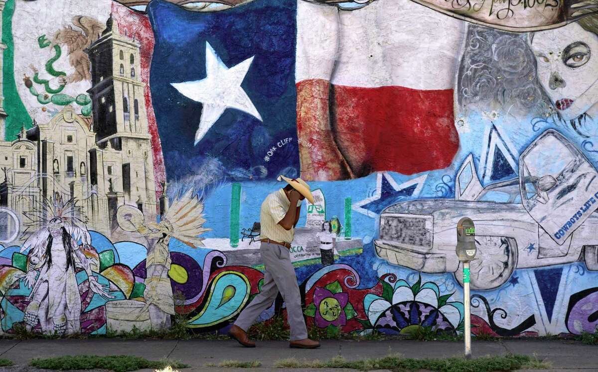 A man adjusts his face mask as he walks past a mural in the heavily Latino section of Oak Cliff in Dallas, Sept. 22, 2021. Texas GOP leaders have unveiled proposed new maps for congressional and state legislative districts. Many Latino advocates and others say the maps fail to reflect role Latinos especially played in fueling the explosive population growth over the past decade in Texas.